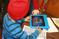 Students using technology at a community event.
