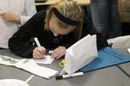 A student works on a craft at Holidays Around the World