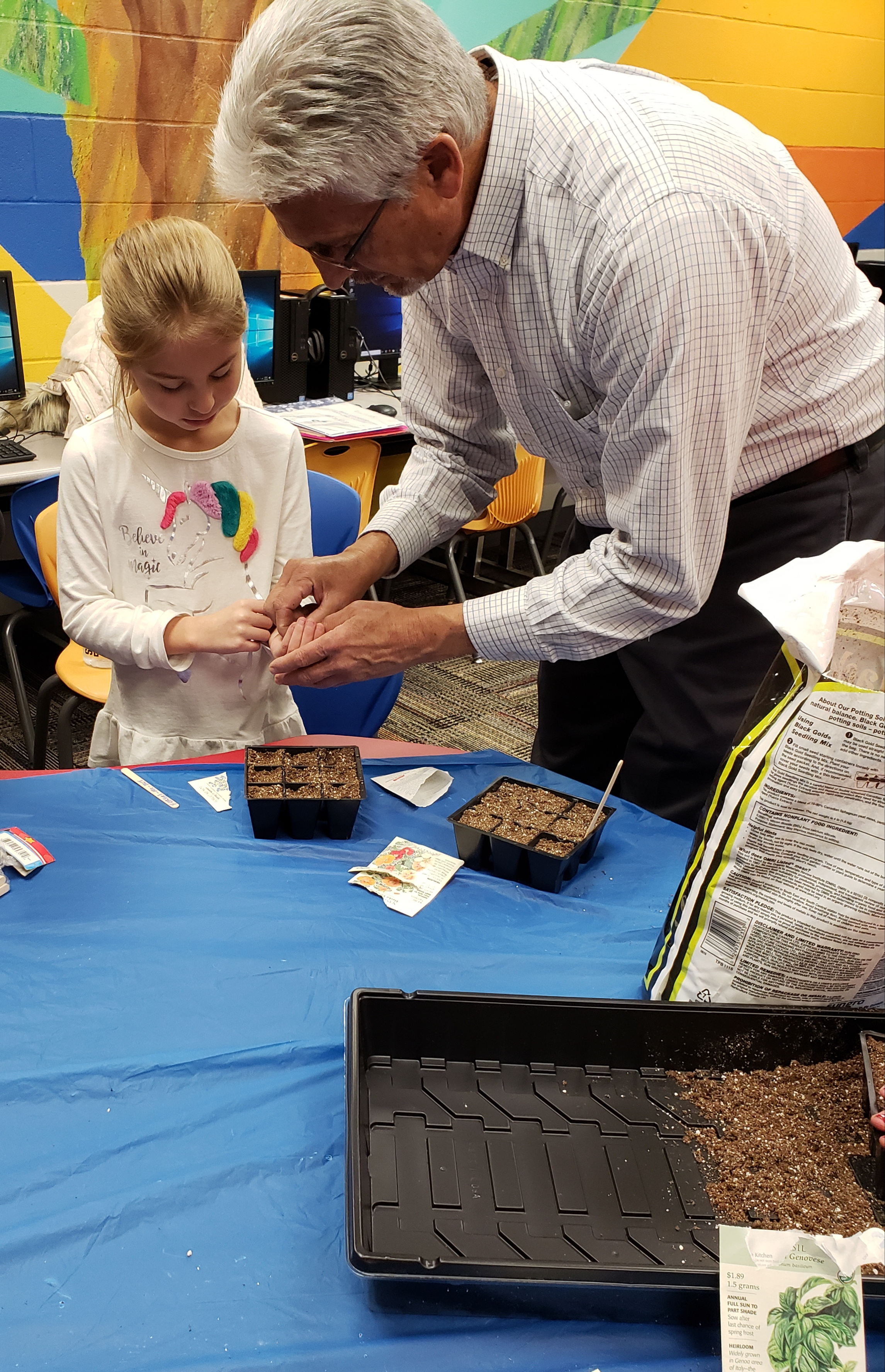Mr. Dan shows Sophia how to plant bulbs